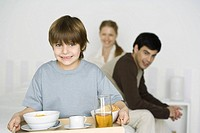 Little boy carrying breakfast on tray, parents sitting on bed in background