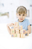 Little girl stacking blocks, looking at camera, portrait