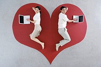 Man and woman lying on large heart graphic, both using laptop computers (thumbnail)