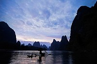 Silhouette of a person in a river with a hill range in the background, Guilin Hills, XingPing, Yangshuo, Guangxi Province, China