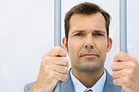 Businessman behind bars, frowning at camera