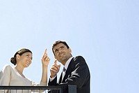 Businessman and businesswoman admiring view, pointing