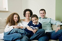 Mixed race family sitting on sofa and smiling