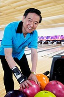 Asian man choosing bowling ball