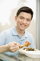 Portrait of a male office worker having lunch and smiling