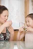 Mature woman with her daughter drinking tea