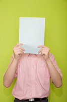 Male office worker hiding his face with a paper