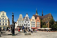 Sculptures at town square with church in background, St Mary´s Church, Rostock, Mecklenburg_West Pomerania, Germany