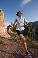 Young woman jogging in mountain setting.