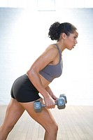 Muscular young woman is exercising with weights in gym