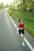 Young woman jogging on rural road