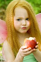Young girl dressed as fairy with an apple