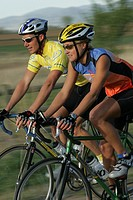 Young man and young woman cycling in rural setting