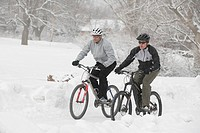 Two men cycling in snow covered park