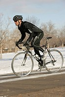 Man cycling on road in snow
