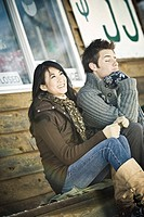Young couple sitting in front of shop in winter