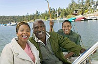Three generation family on fishing trip smiling portrait