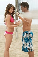 Couple Flirting on Beach with volleyball net between them woman holding ball against her boyfriend