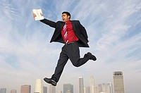 Business man jumping with newspaper over city