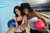 Young women at bowling alley holding balls portrait
