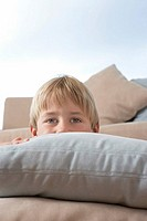 Young Boy Hiding Behind Pillows and cushions