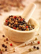 Mixed peppercorns in and beside a mortar