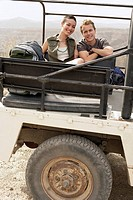 Young couple sitting in back of four wheel drive car in desert portrait