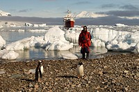 Antarctica, Antarctic Peninsula, Gerlache strait, Neko Harbor, Antarctic Dream ship, Chilean ornithologist Rodrigo Tapia with Gentoo Penguins. MR.