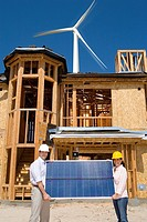 Couple holding solar panel on construction site