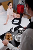 High angle view of a businesswoman sitting on the bed and a waiter serving breakfast