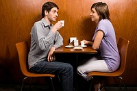 Side profile of a young couple having coffee in a cafe