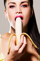 Portrait of a young woman eating a banana