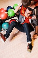 High angle view of a young man gripping another young man´s neck in a bowling alley