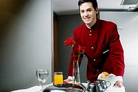 Portrait of a waiter pushing the trolley of breakfast