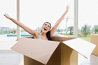 Young woman sitting in a cardboard box and laughing
