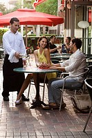 Young couple sitting in a sidewalk cafe and smiling