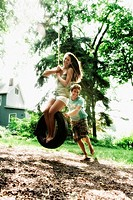 Teenage girl swinging on a tire swing with a young man pushing her