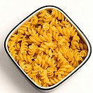 High angle view of a bowl of raw fusilli pasta