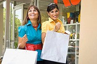 Mature woman with her daughter holding shopping bags and smiling