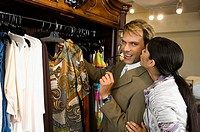 Young woman kissing a mid adult man in a clothing store