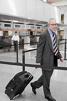 Side profile of a businessman pulling his luggage