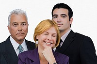 Close_up of a businesswoman smiling with two businessmen behind her