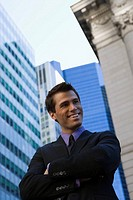 Low angle view of a businessman standing with his arms crossed and smiling