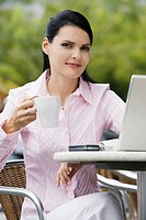 Portrait of a businesswoman sitting on a chair and holding a cup of coffee