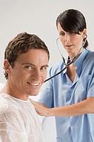 Female surgeon examining a mid adult man