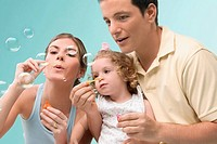 Mid adult couple blowing bubbles with their daughter