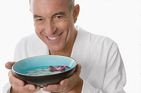 Close_up of a senior man holding a bowl and smiling