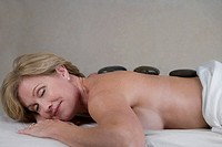 Side profile of a mature woman lying on a massage table with her eyes closed
