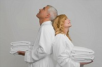Side profile of a mature couple standing back to back and holding folded towels