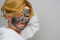 Portrait of a mature woman wearing facial masks and smiling